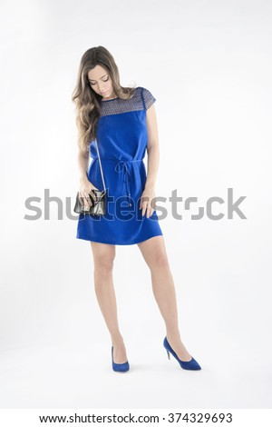 female fashion model wearing blue dress,blue shoes,black purse against light-grey background