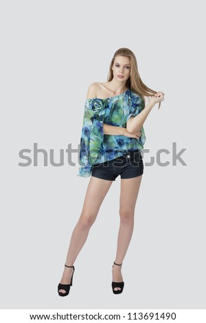 female fashion model with blond hair and blue eyes posing at light background - stock photo