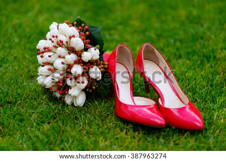 Female fashion red wedding shoes with bride's bouquet of white tulips flowers and red berries on green grass background. - stock photo