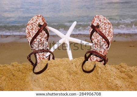 Female Fashion Rubber Heel-Strap Sandals And Starfish On The Summer  Beach Close-up. Sea On The Background - stock photo