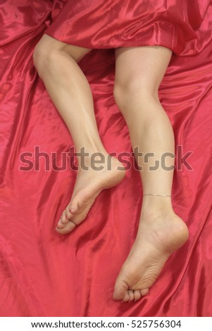 Female feet and legs over red background