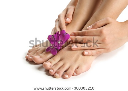 Female feet at spa pedicure procedure with flower isolated on white - stock photo