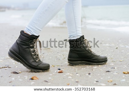 Female feet in blue jeans and black winter boots are on the beach sand - stock photo