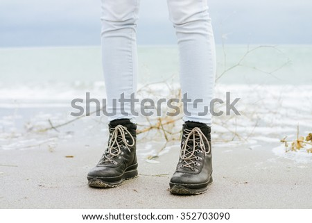 Female feet in blue jeans and black winter boots standing in the sand against the sea - stock photo