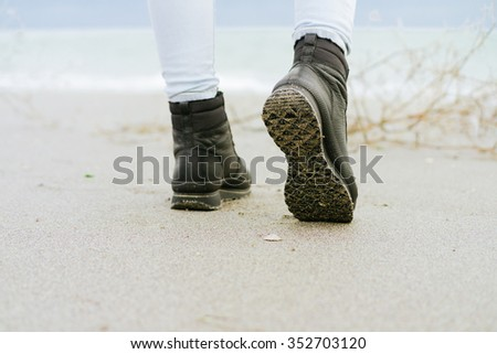 Female feet in blue jeans and black winter boots standing on the beach against the sea - stock photo