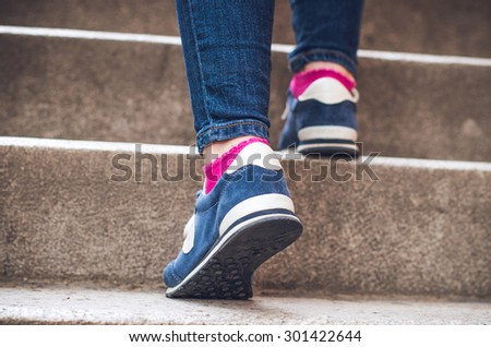 Female feet in denim sneakers on the stairs