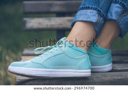 Female feet in jeans and sports shoes. Sneakers are on a wooden bench in a park close-up. Woman resting on the bench after the walk. - stock photo