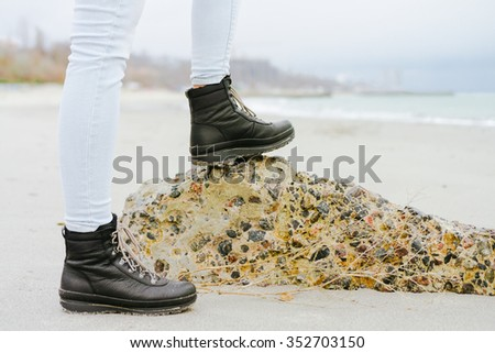 Female feet in jeans and winter boots standing on a stone on the coast. - stock photo