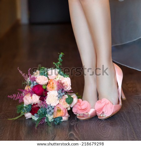 female feet in pink wedding sandals with a wedding bouquet  - stock photo