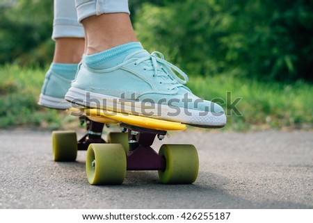 Female feet in sneakers on a yellow skateboard closeup