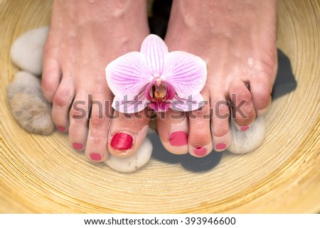 Female feet in spa bowl with sea salt, foot bath. - stock photo