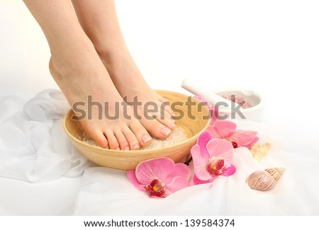 Female feet in spa bowl with sea salt, isolated on white - stock photo