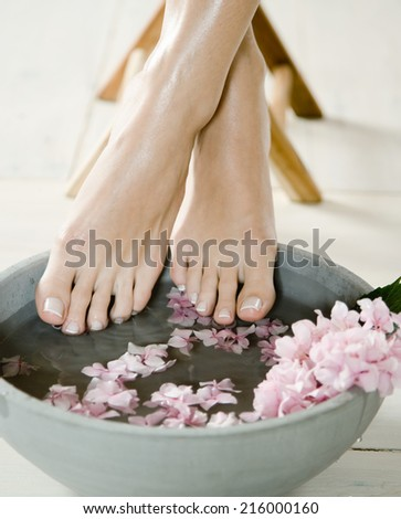 Female feet in spa bowl with water - stock photo