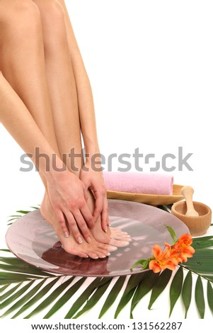 Female feet in spa bowl with water, isolated on white