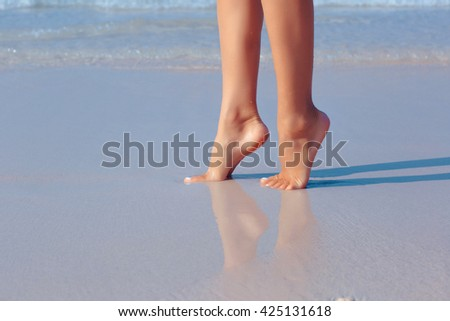 Female feet in water on the beach, white sand