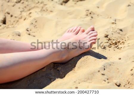 Female feet on a sand - stock photo