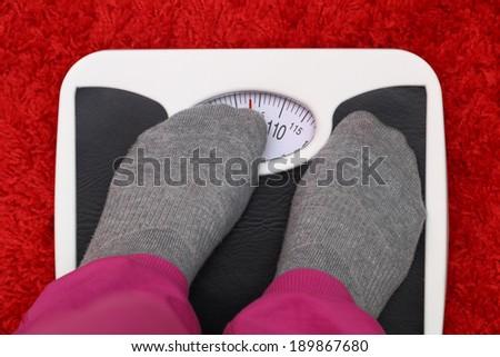 Female feet on bathroom scale - stock photo