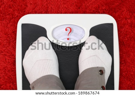 Female feet on bathroom scale with question mark symbol - stock photo