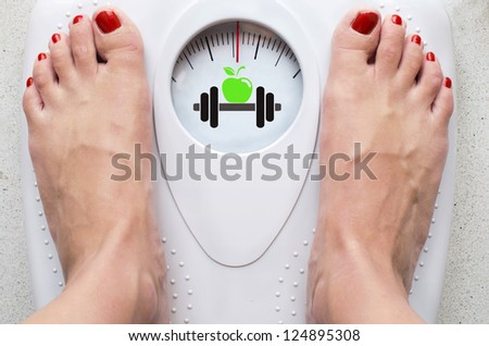 Female feet on bathroom scale with symbols for diet and fitness - stock photo