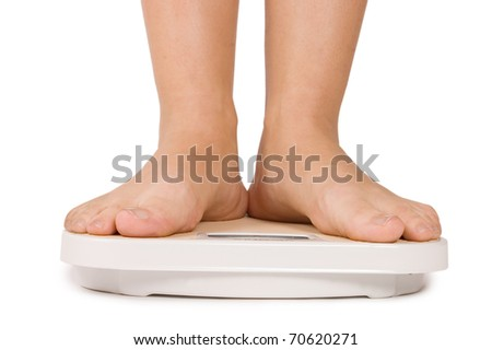 Female feet on scales isolated on white