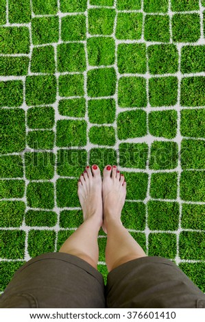 Female feet on the grass. Girl stand on green lawn. Picture your feet on top. Conceptual photo, point of view perspective. - stock photo