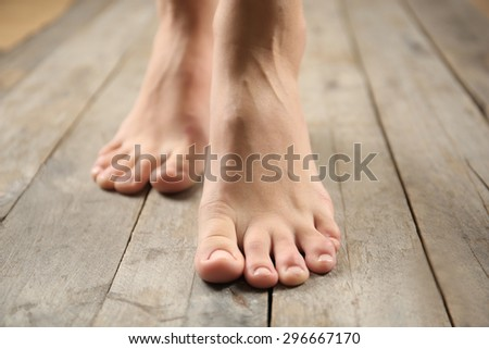 Female feet on wooden background - stock photo