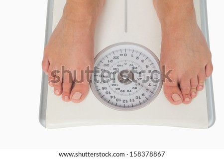 Female feet standing on a scales on white background