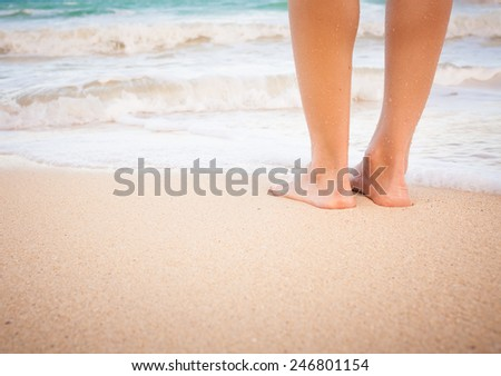 Female feet standing on the beach.