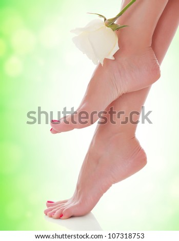 Female feet with a flower on green blurred background