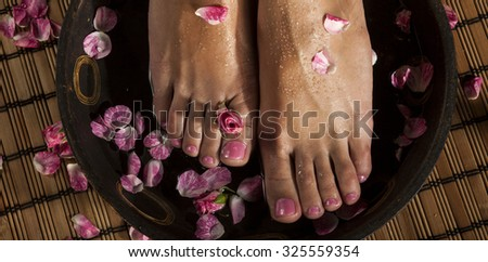Female feet with drops of water in spa bowl with water and roses.