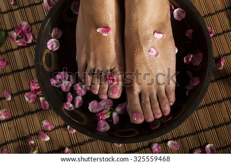 Female feet with drops of water in spa bowl with water and roses. - stock photo