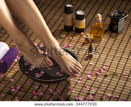 Female feet with drops of water, spa bowl, towels, flowers and candles. - stock photo