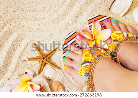 Female feet with pretty multicolor pedicure on sand, with frangipani flowers and seashells. Summertime concept, top view - stock photo