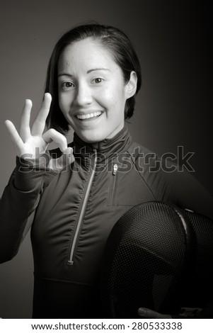 Female fencer showing ok sign - stock photo