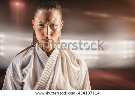 Female fighter on black background against composite image of playing field indoor - stock photo