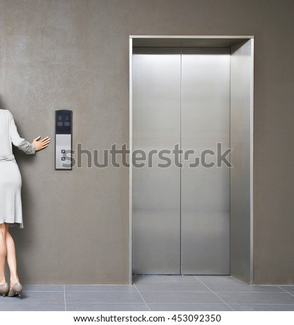 female finger pushing elevator button