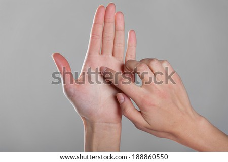 Female finger touches an open hand on gray background.