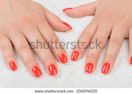 female fingers with red enamel
