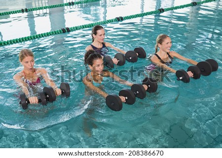 Female fitness class doing aqua aerobics with foam dumbbells in swimming pool at the leisure centre - stock photo