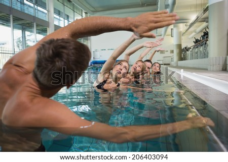Female fitness class doing aqua aerobics with male instructor in swimming pool at the leisure centre - stock photo