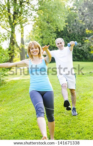 Female fitness instructor exercising with middle aged man outdoors in green park