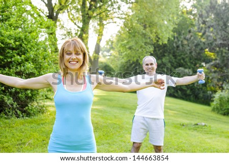 Female fitness instructor exercising with middle aged man outdoors in summer park - stock photo