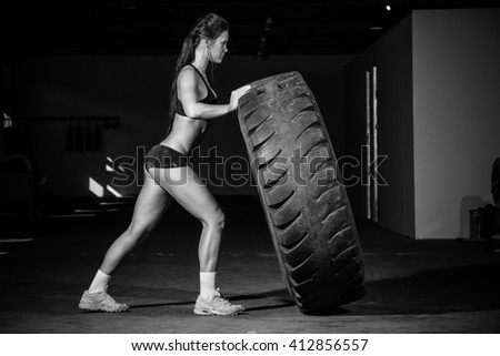 Female fitness model flipping a tyre during an intense training session in a gym.
