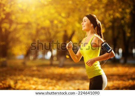 Female fitness model training outside on a warm fall day and listening to music. Sport lifestyle. - stock photo