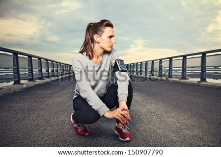 Female fitness runner sitting alone on the bridge resting - stock photo