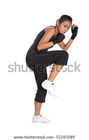 Female fitness trainer in fighting pose with one leg in air in self protect position.