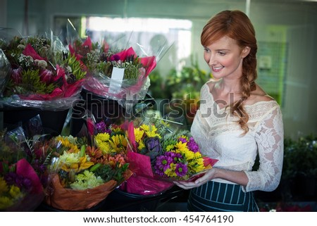 Female florist arranging flower bouquet in the flower shop - stock photo