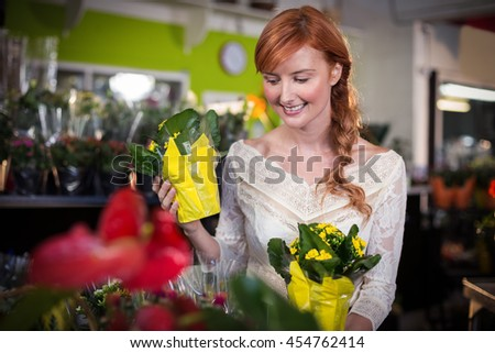 Female florist holding flower bouquet in the shop - stock photo