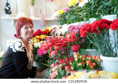Female florist in her small  flower shop - stock photo