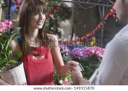 Female florist receiving credit card from customer in shop - stock photo
